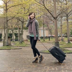 Japanische Frauen: Junge Frau mit Koffer telefoniert vor einem Haus