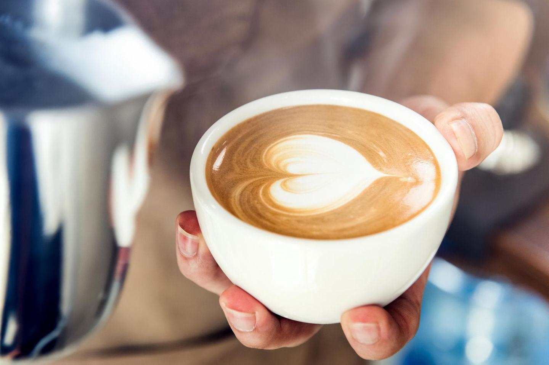 Kaffee-Alternativen: Barista hält Tasse mit Latte Art-Muster