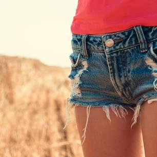Junge Frau mit ripped Jeansshort auf Feld stehend
