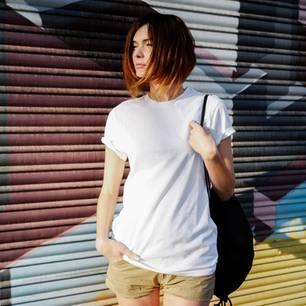 Junge Frau in weißen T-Shirt steht vor Graffiti-Wand
