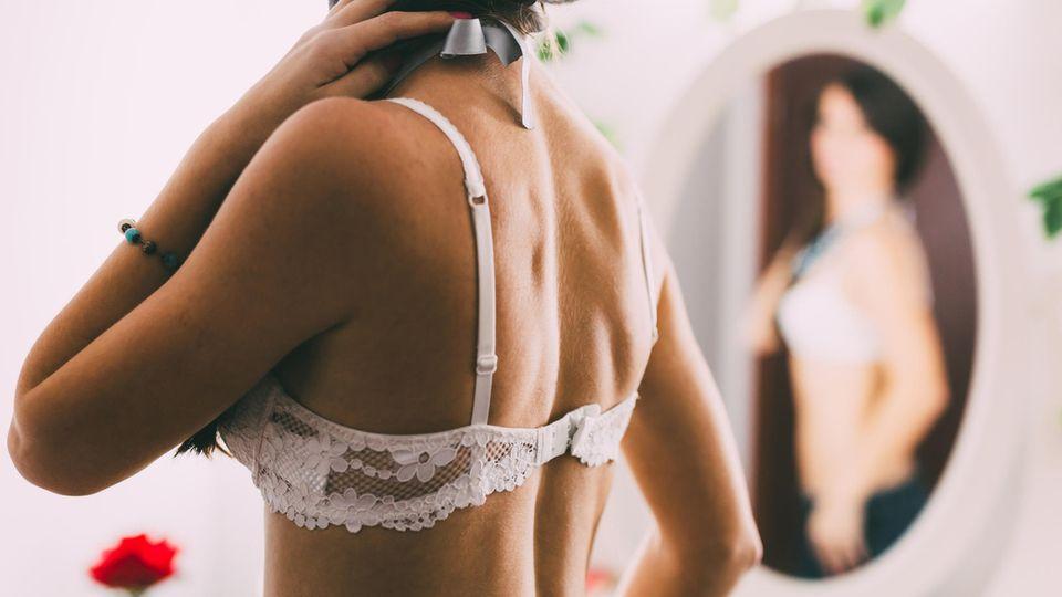 Wie oft muss man den BH wechseln? Frau im BH steht vor dem Spiegel