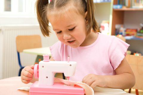 Nähen mit Kindern: Mädchen sitzt an Nähmaschine