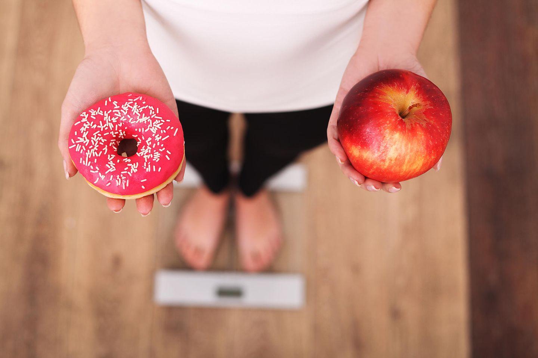 Montignac-Methode: Frau hält in der einen Hand einen Donut und in der anderen einen Apfel