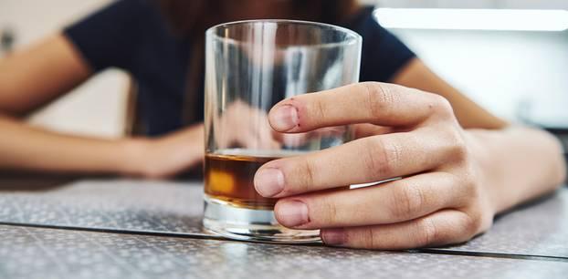 Alkohol-Allergie: Frau hält Drink und fühlt sich sichtlich unwohl