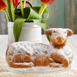 Osterlamm: Kuchen in Lammform vor Blumenstrauß