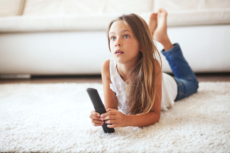Mädchen vorm Fernseher mit Fernbedienung