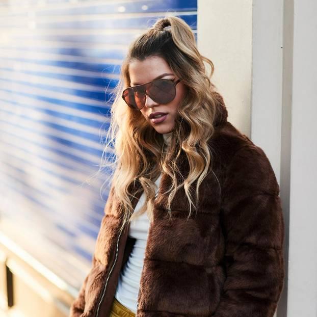 Frühlingsfrisuren: Junge Frau mit welligen Haaren lehnt an der Wand