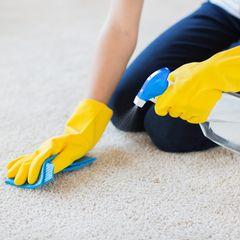 Teppich reinigen: Frau kniet auf Teppich und entfernt Flecken
