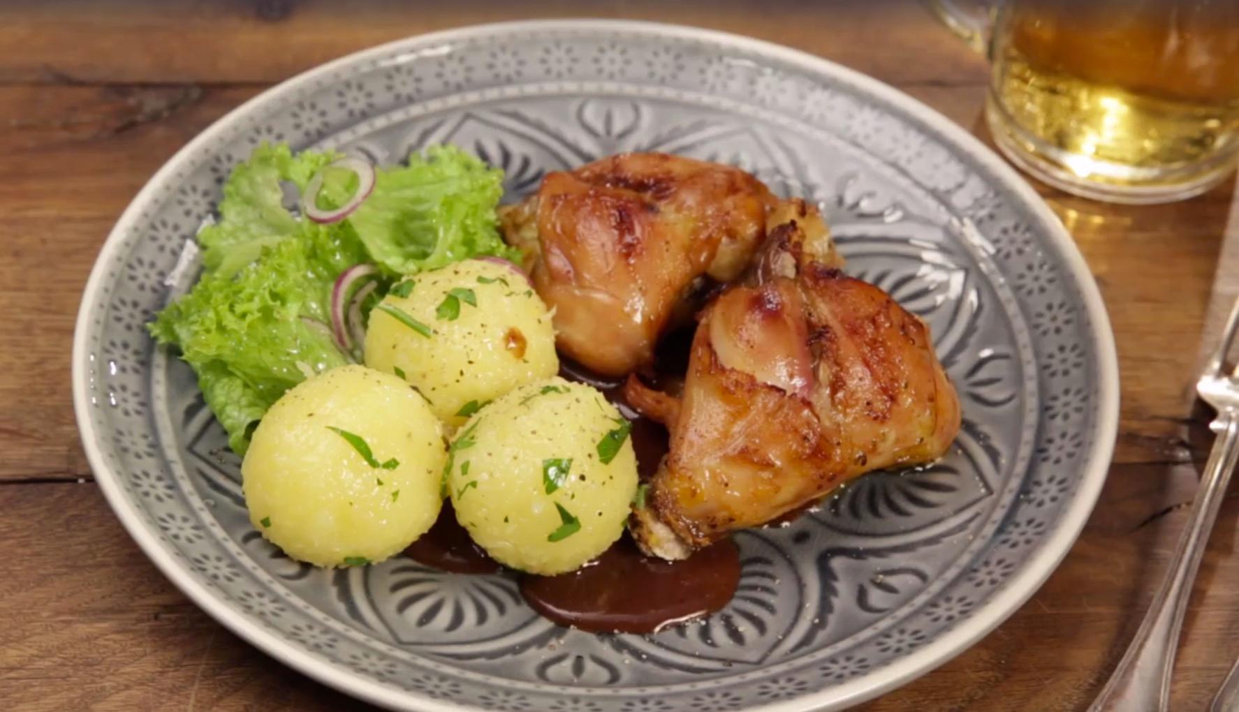 Kaninchenbraten serviert mit Klößen und Soße