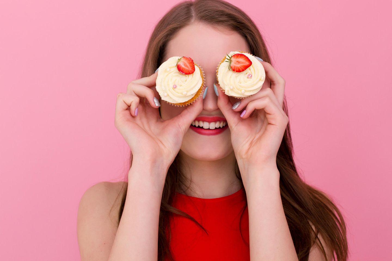 FdH: Frau hält sich zwei Cupcakes mit Erdbeeren vor die Augen, grinst