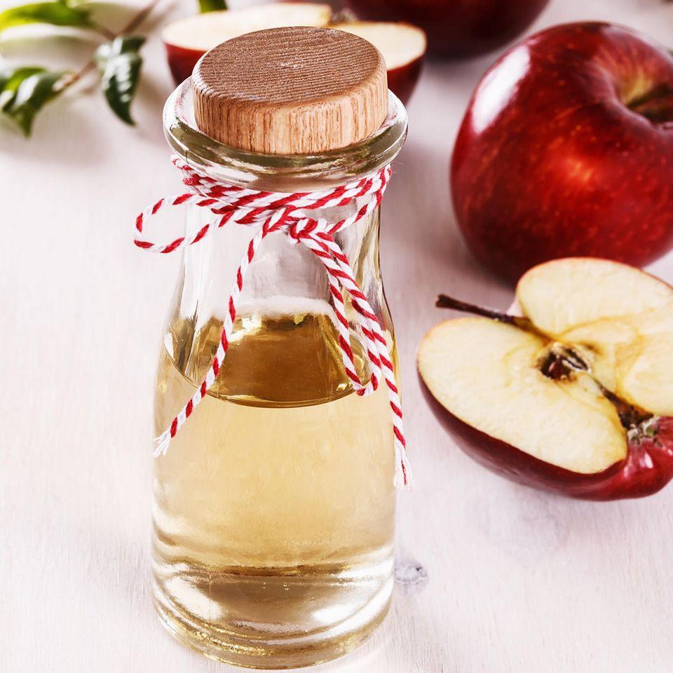 Apfelessig-Diät: Apfelessig in einer Glasflasche, daneben drapierte Äpfel