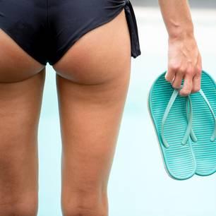 Was hilft gegen Cellulite? Frau am Strand in Bikinihose