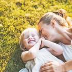 Mutter knuddelt mit Kind im Gras