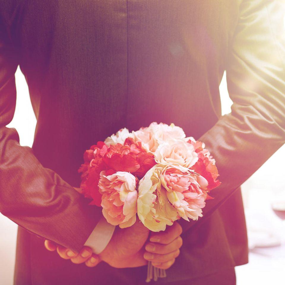 Hochzeitstage: Mann hält Blumen hinter seinem Rücken
