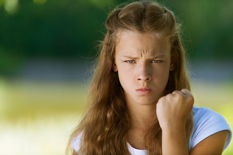 Partyzwang: Mädchen guckt wütend in die Kamera und hebt die Faust