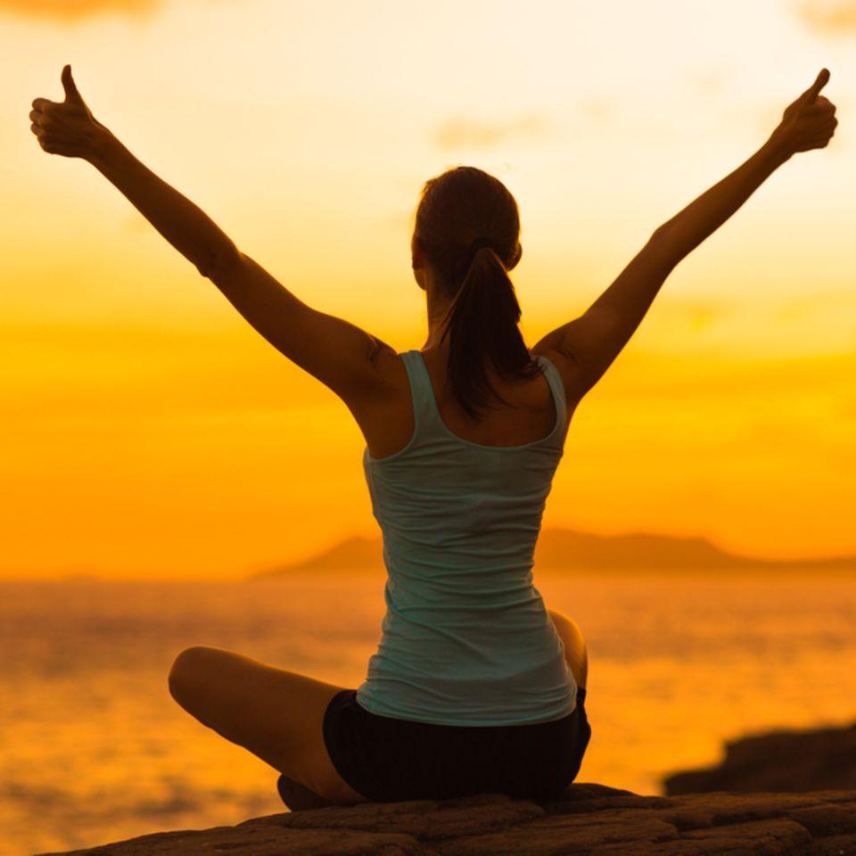 Junge Frau sitzt im Schneidersitz vor Sonnenuntergang