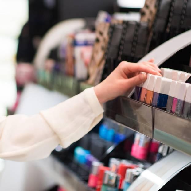 Frau steht in der Drogerie und benutzt Beauty-Tester