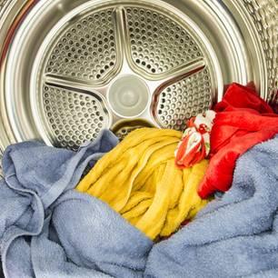 Flusensieb reinigen: Handtuchstapel liegt im Wäschetrockner