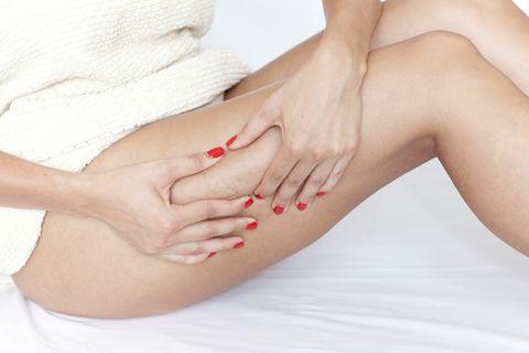 Massage gegen Cellulite: Frau massiert ihre Oberschenkel