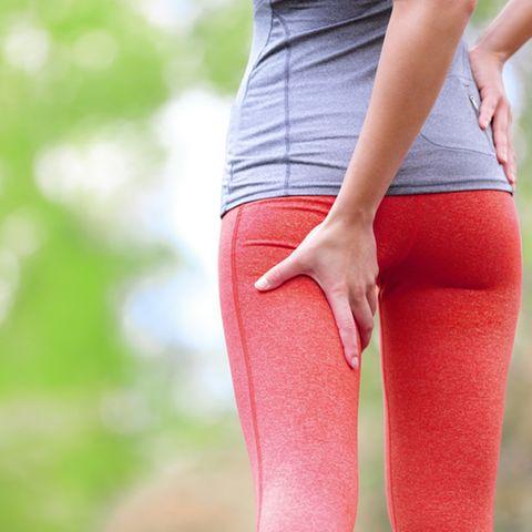 Cellulite bekämpfen: Joggerin greift sich an den Oberschenkel