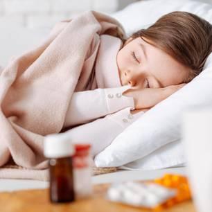 Krankes Mädchen in Bett eingemummelt.