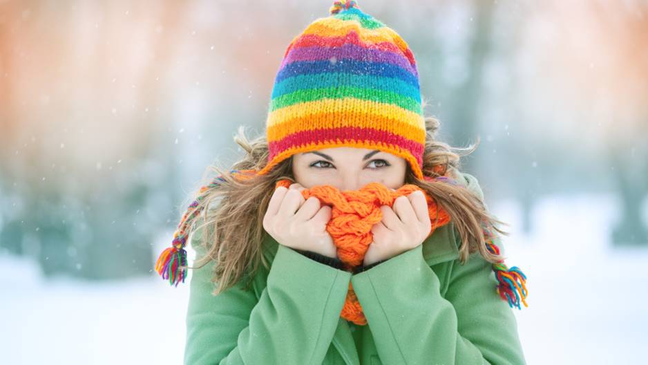 Frieren: Frau in Mütze steht im Schnee