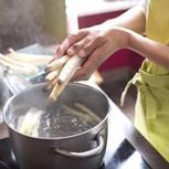 Spargel-Kochzeit: Frau legt Spargel in einen Topf