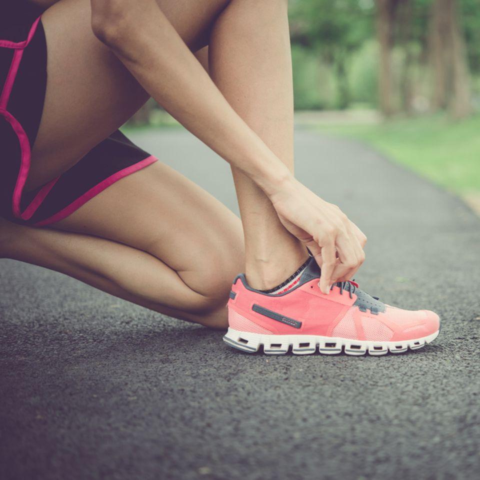 Bindegewebe stärken: Frau bindet ihre Laufschuhe