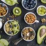 Glyx Diät: Schalen mit Müsli, Nüssen und Beeren auf dunklem Untergrund