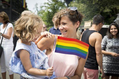 Berlin: Ein kleines Mädchen auf dem Arm seiner Mutter mit einer LGBT-Fahne in der Hand