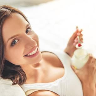 Schwangere isst lächelnd Joghurt