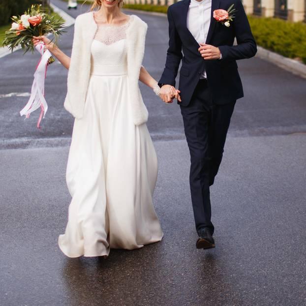 England: Ein Brautpaar läuft Hand in Hand durch einen Vorort