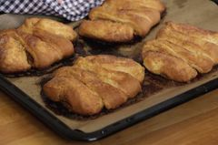 Franzbrötchen kommen auf einem Blech aus dem Ofen