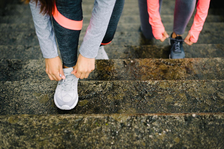 Sport ab 40: Bildausschnitt zweier Frauen, die sich die Sportschuhe zubinden