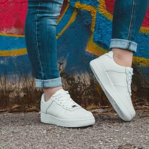 Frau mit weißen Sneakern steht vor Graffitti-Wand