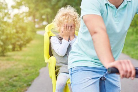 Kind sitzt in Heckfahrradsitz und hält sich Augen zu