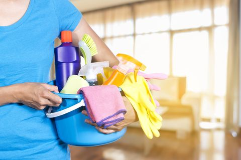 Studie: Eine Frau mit einem Putzeimer voll Reinigungsmitteln und Putzutensilien
