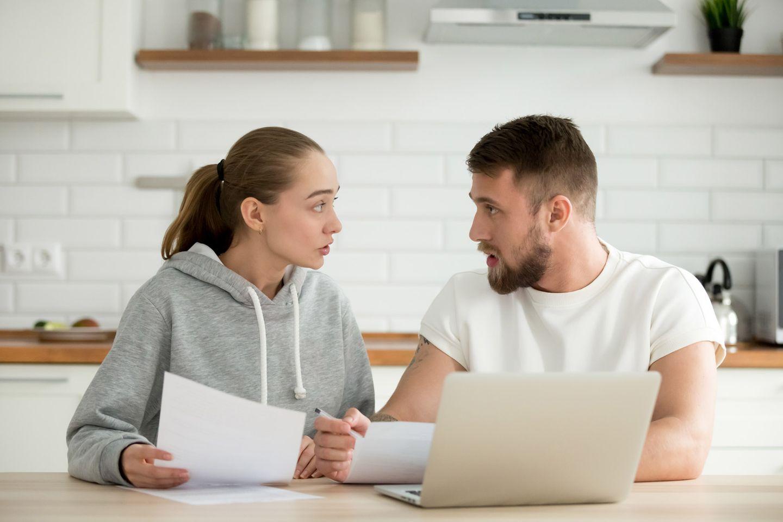 Geldstress in der Beziehung: Paar streitet sich am Küchentisch