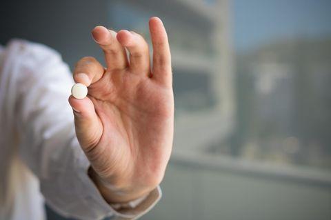 Abtreibungspille ins Essen gemischt: Hand mit Tablette