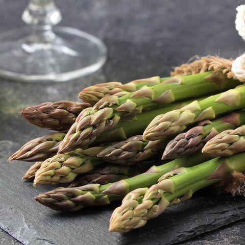 Grüner Spargel: Spargelstangen eingwickelt auf dem Küchentisch mit Wein