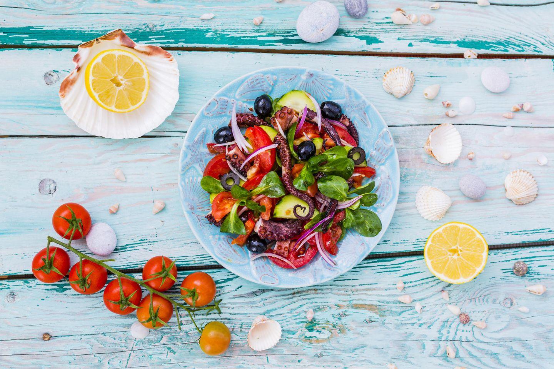 Mittelmeerdiät: Muscheln, Zitronen, Tomaten und ein Teller mit Salat und Octopus