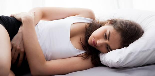 Eileiterschwangerschaft: Frau liegt und hält sich schmerzenden Unterbauch fest
