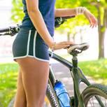 Schwaches Bindegewebe: Frau in kurzer Hose steht an ihrem Fahrrad