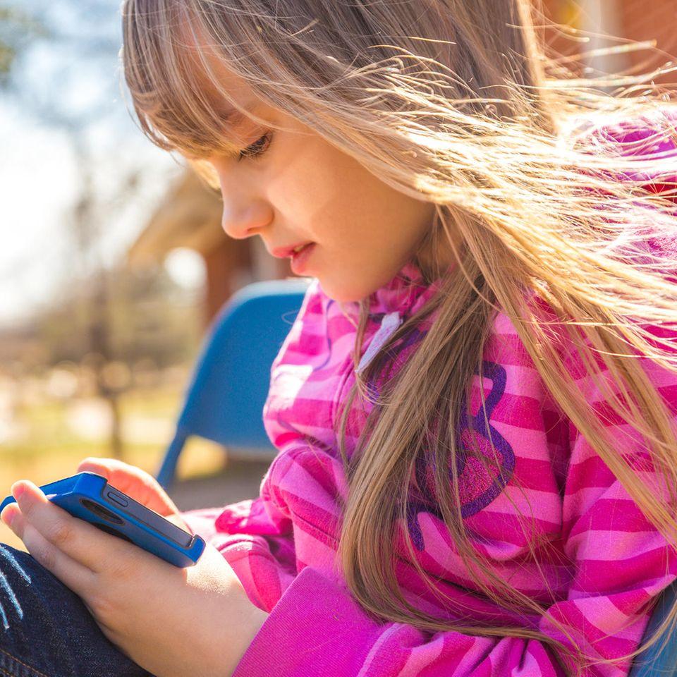 Trauer: Ein kleines Mädchen mit einem Handy auf einer Bank im Park