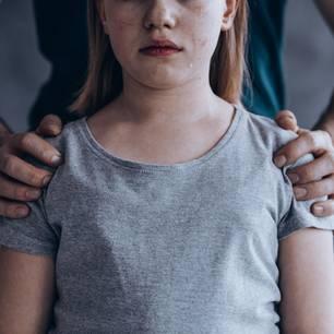 Facebook: Ein Mann hält ein ängstliches Mädchen von hinten an den Schultern fest