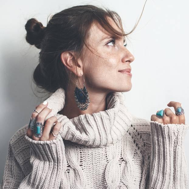 Junge Frau mit Ringen und großen Statementohrringen
