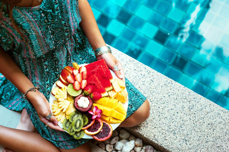Raw Till Four: Frau hält Schale mit Obst im Schoß