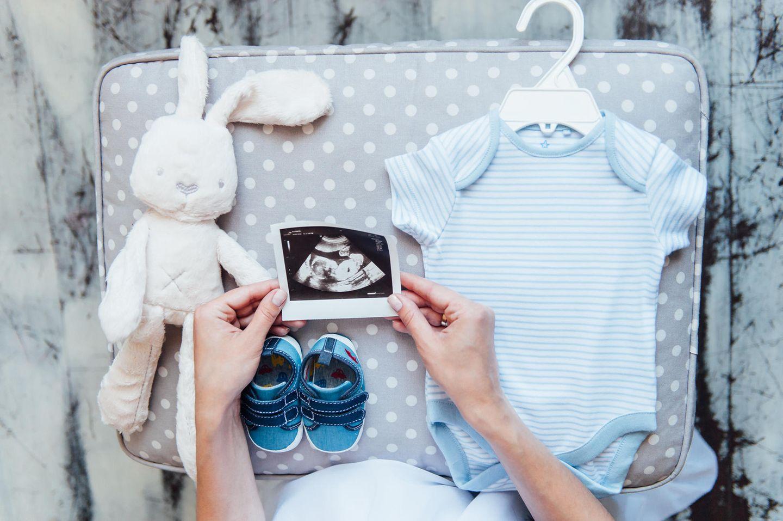Ultraschallbild vor Babykleidung und Plüschhaase drapiert.