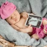 Schlafendes Neugeborenes mit Ultraschallbild in der Hand drapiert.