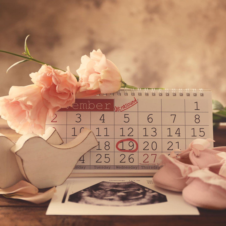 Ultraschalbild liegt vor mit Blumen und Babyschuhen verziertem Kalender